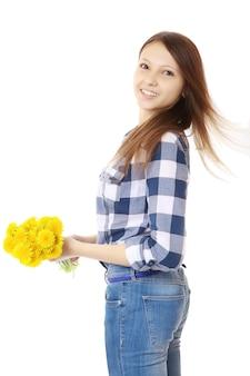 Dziewczyna ubrana w dżinsy i koszulę w kratę, trzyma żółte kwiaty.