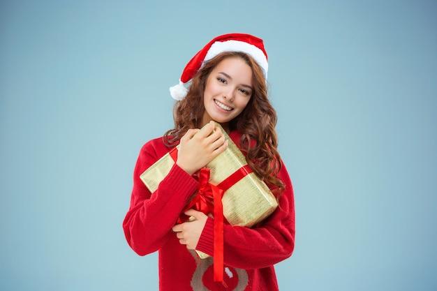 Dziewczyna ubrana w kapelusz santa z prezentem na boże narodzenie