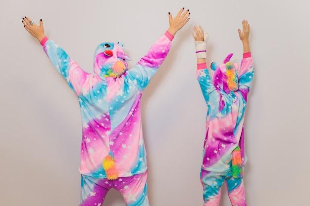 Dziewczyna ubrana w kostium kigurumi jednorożca, przygotowująca się na imprezę cosplay lub sen. odziana w piżamę młoda dama patrzeje kamerę podczas gdy pozujący przeciw białemu tłu.