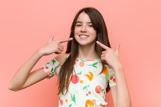 Dziewczyna ubrana w letnie ubrania na czerwonej ścianie uśmiecha się, wskazując palcami na usta.