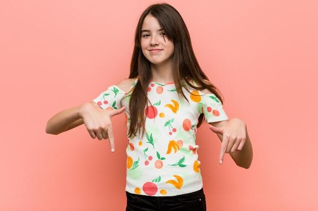 Dziewczyna ubrana w letnie ubrania na czerwonej ścianie wskazuje palcami, pozytywne uczucie.