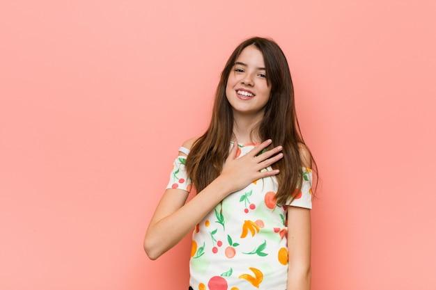 Dziewczyna ubrana w letnie ubrania na różowej ścianie śmieje się głośno, trzymając rękę na piersi