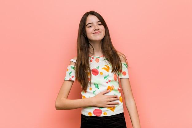 Dziewczyna ubrana w letnie ubrania przy ścianie dotyka brzucha, uśmiecha się delikatnie, je i satysfakcję.