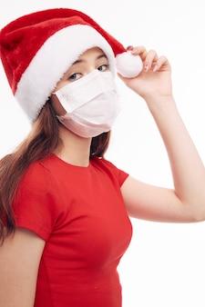 Dziewczyna ubrana w maskę medyczną santa hat świąteczna czerwona koszulka