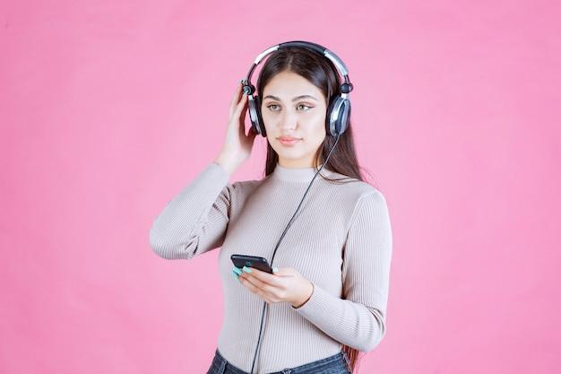 Dziewczyna ubrana w słuchawki i ustawianie muzyki w swoim smartfonie