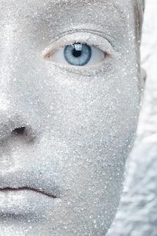 Dziewczyna ubrana w srebrny brokatowy makijaż