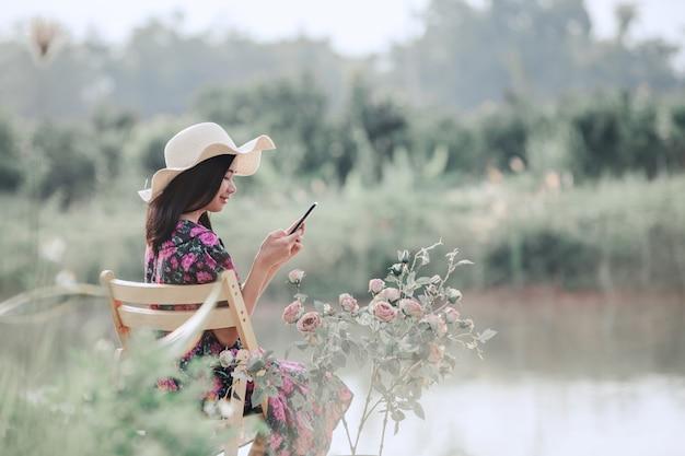 Dziewczyna ubrana w sukienkę kwiatowy siedzi w przyrodzie