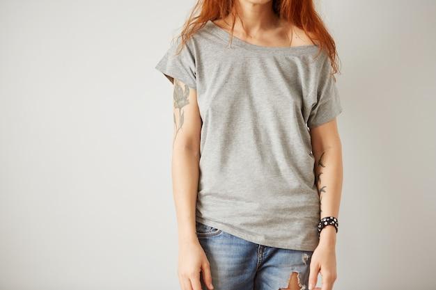 Dziewczyna ubrana w szary t-shirt pusty stojący na białej ścianie