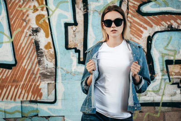 Dziewczyna ubrana w t-shirt i bawełnianą kurtkę pozuje przeciwko ulicy