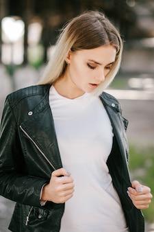Dziewczyna ubrana w t-shirt i skórzaną kurtkę pozuje przeciwko ulicy
