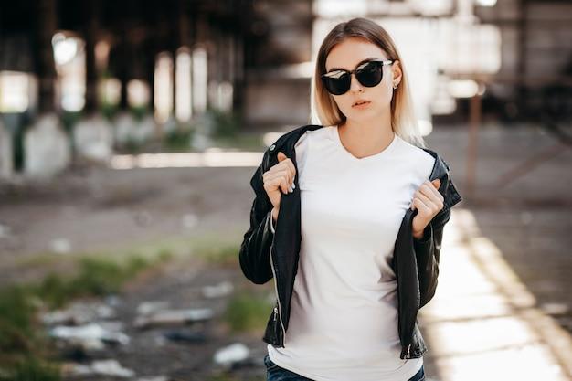 Dziewczyna ubrana w t-shirt, okulary i skórzaną kurtkę pozuje przeciwko ulicy