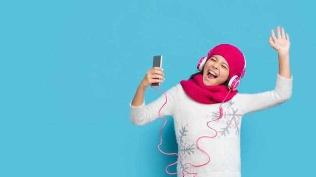Dziewczyna ubrana w zimowe ubrania słuchania muzyki