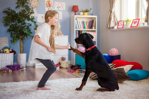 Dziewczyna ucząca psa, jak przybijać piątkę