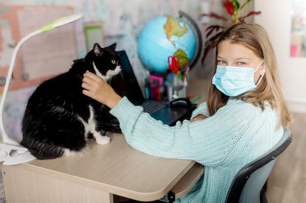 Dziewczyna ucząca się na odległość głaszcząca kota w domu
