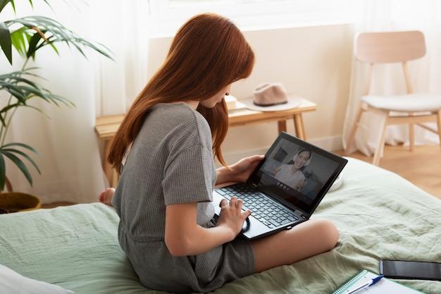 Dziewczyna ucząca się za pomocą średniego strzału z laptopa