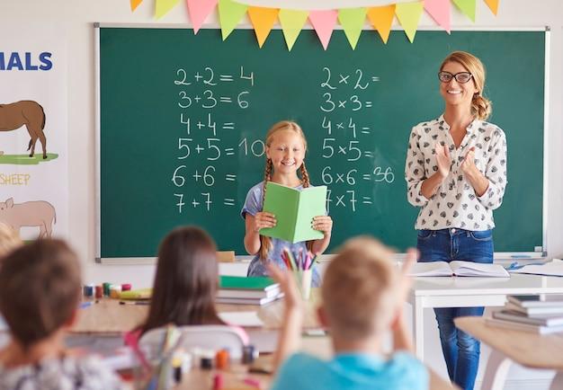 Dziewczyna uczeń klaska nauczyciela