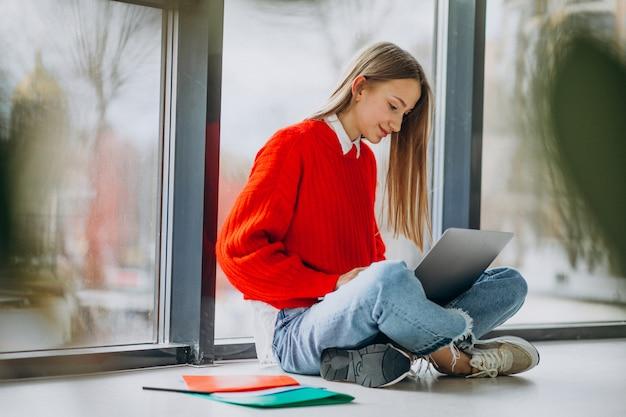 Dziewczyna uczeń studiuje na komputerze okno