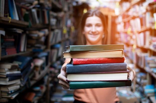 Dziewczyna uczeń trzyma stertę książki w bibliotece