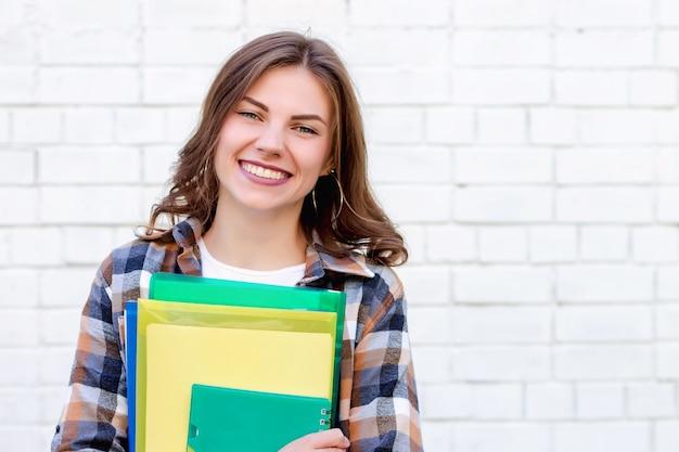 Dziewczyna uczeń trzyma w rękach falcówki i notatnika i ono uśmiecha się na tle biały ściana z cegieł