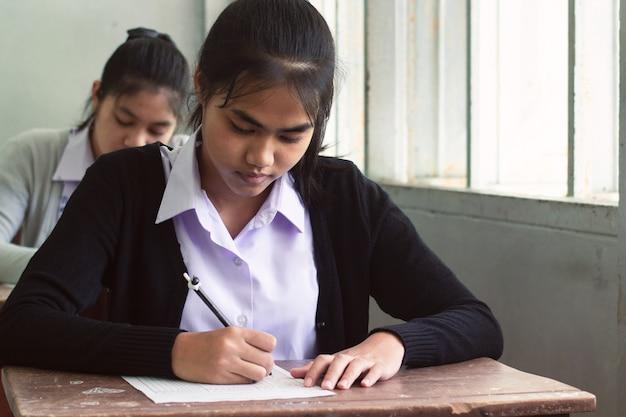 Dziewczyna uczeń uśmiecha się egzamin i pisze