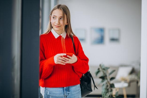 Dziewczyna uczeń w czerwonym pulowerze używać telefon
