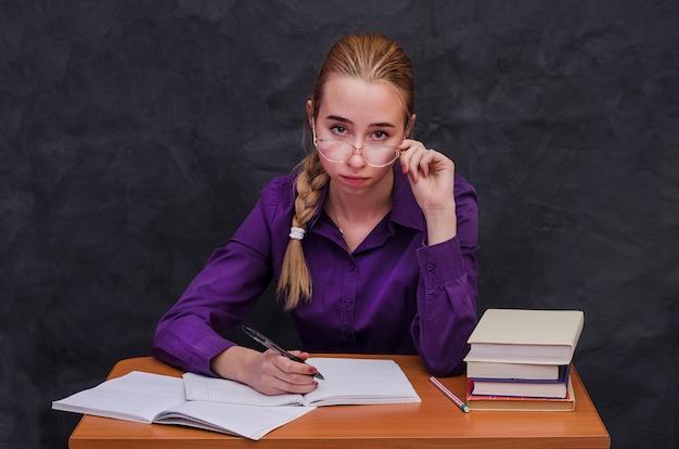 Dziewczyna uczeń w szkłach siedzi przy stołem z notatnikami i książkami