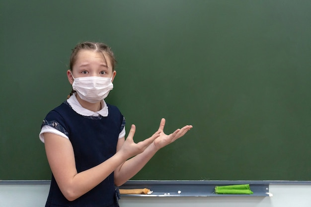 Dziewczyna uczennica w masce medycznej stoi przy tablicy i pokazuje ręce na wolnym miejscu.