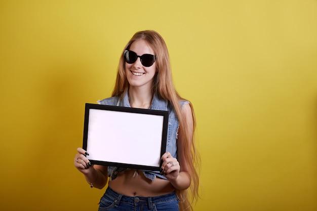 Dziewczyna ucznia chwyta pustego miejsca biała deska. modelka.