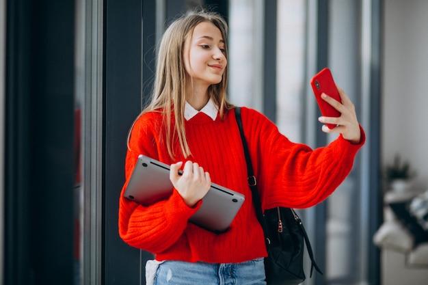 Dziewczyna ucznia mienia komputer i opowiadać na telefonie okno
