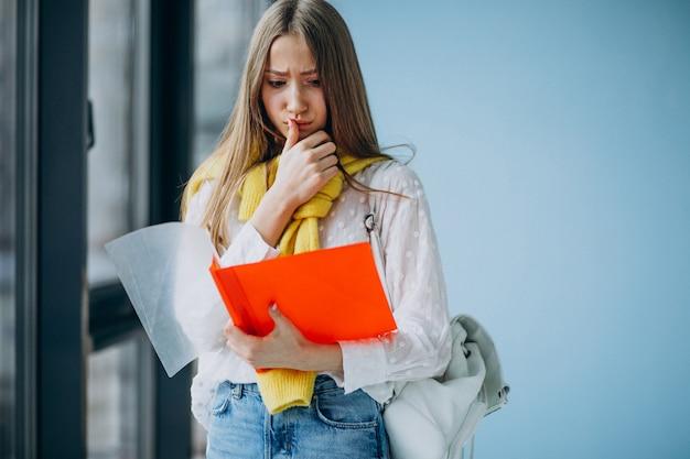 Dziewczyna ucznia pozycja z kolorowymi falcówkami