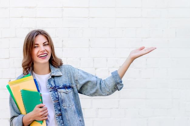Dziewczyna ucznia punktów ręka przy ścianą. dziewczyna pokazuje palec wskazujący na tle