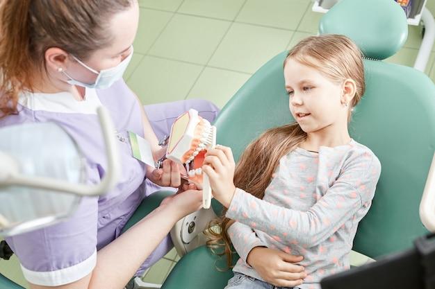 Dziewczyna uczy dentysty, jak myć zęby. stomatolog dziecięcy edukujący dziecko w zakresie szczotkowania zębów na modelu.