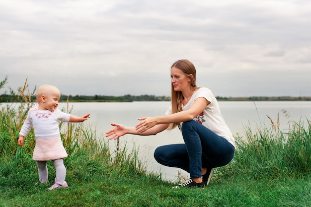 Dziewczyna uczy się chodzić z matką w naturze. mama i córka, nauka i rozwój. pierwsze kroki dziecka. szczęśliwe chwile życia.