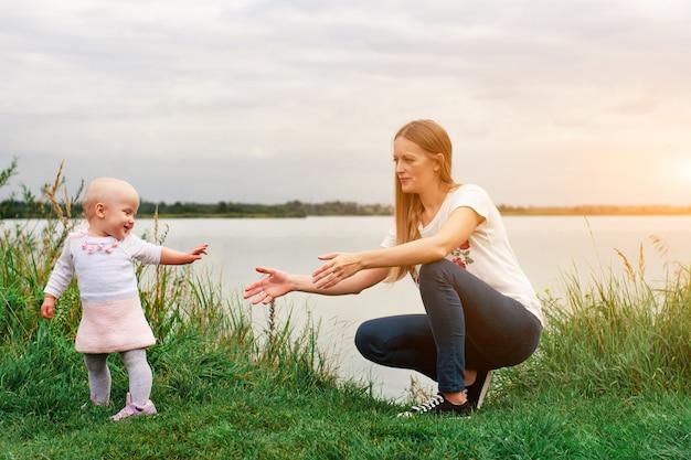 Dziewczyna uczy się chodzić z matką w naturze. mama i córka, nauka i rozwój. pierwsze kroki dziecka.