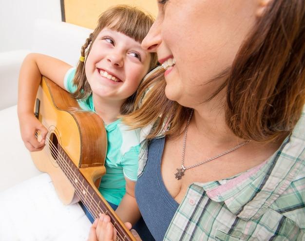 Dziewczyna uczy się grać na gitarze przy wsparciu mamy w domu
