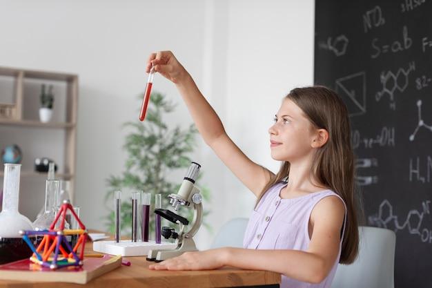 Dziewczyna uczy się więcej o chemii w klasie