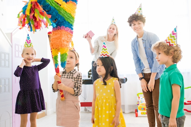 Dziewczyna uderzająca pinata na przyjęciu urodzinowym