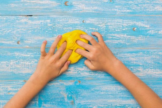 Dziewczyna ugniata kulkę żółtej slaymy na niebieskim drewnianym stole.