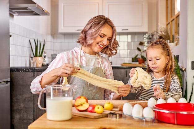 Dziewczyna ugniata z mamą w kuchni