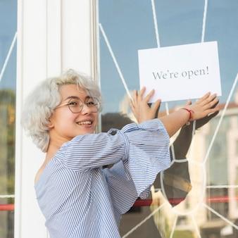 """Dziewczyna umieszczająca na drzwiach napis """"jesteśmy otwarci"""""""