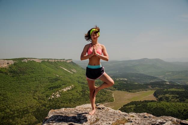 Dziewczyna uprawia jogę na szczycie góry. zdrowy tryb życia.