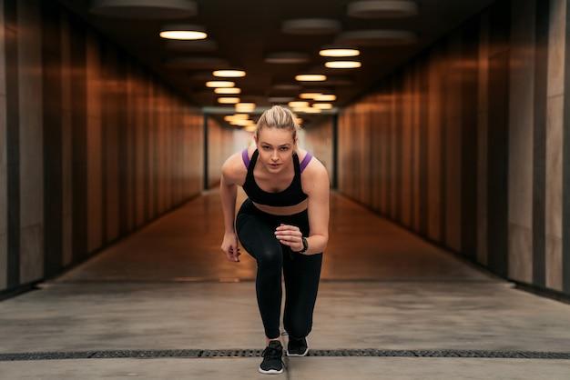 Dziewczyna uprawia sport na ulicy, czarna odzież sportowa, kobieta w sportowych bluzach, kobieta zaczyna biegać