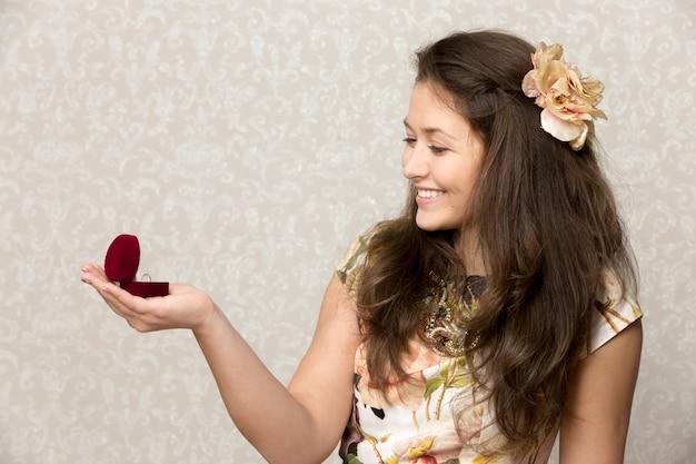 Dziewczyna uśmiecha patrząc przypadek pierścień
