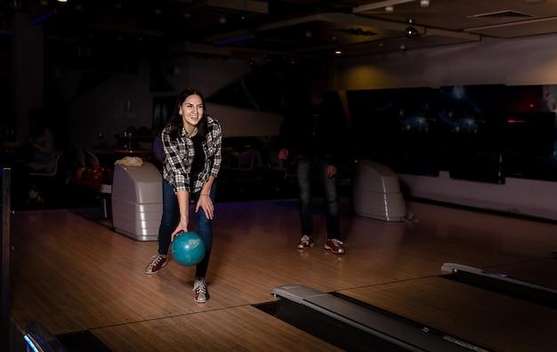Dziewczyna uśmiecha się i gra w kręgielni