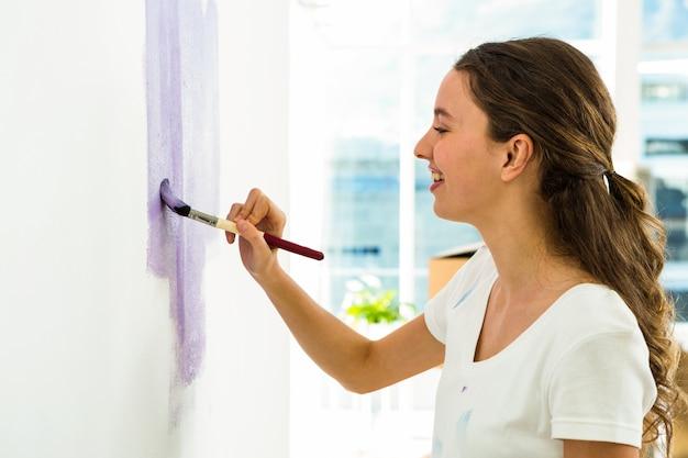 Dziewczyna uśmiecha się i maluje ścianę