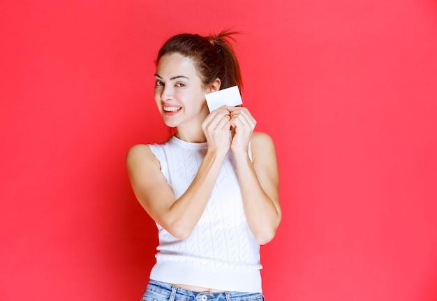 Dziewczyna uśmiecha się i prezentuje swoją wizytówkę.