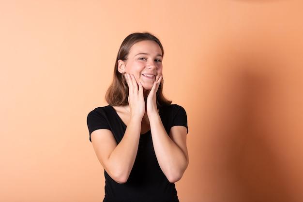 Dziewczyna uśmiecha się i przykłada dłonie do twarzy na jasnopomarańczowym tle. w dowolnym celu.
