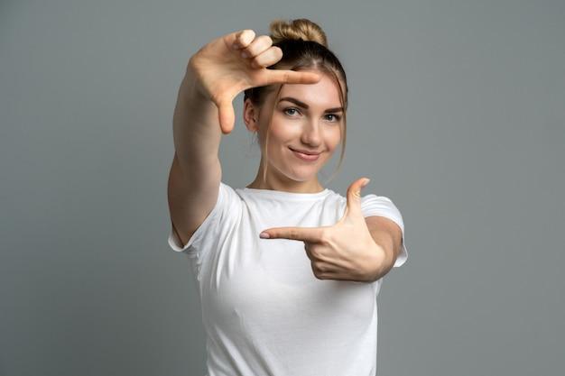Dziewczyna uśmiecha się i robi ramkę imitację palcami
