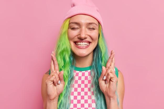 Dziewczyna uśmiecha się radośnie do kamery krzyżuje palec, aby spełnić życzenie ma zamknięte oczy czuje się podekscytowany, widząc szczęśliwy wynik nosi kapelusz w kratkę na różowym tle