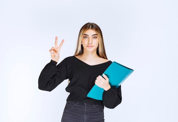 Dziewczyna uzupełniła pliki w niebieskim folderze i poczuła się usatysfakcjonowana. zdjęcie wysokiej jakości
